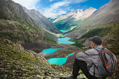 Hiker with backpack sitting on top of the mountain Stock Photo