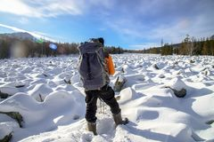 Hiker with backpack on the snow field of stones at he way to the mountains, back view. Royalty Free Stock Photos