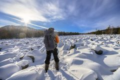 Hiker with backpack on the snow field of stones at he way to the mountains, back view. Royalty Free Stock Photo