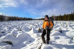 Hiker with backpack on the snow field of stones at he way to the rocky mountains Royalty Free Stock Image