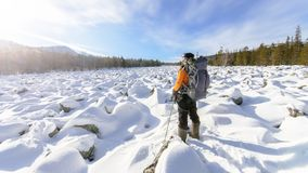 Hiker with backpack on the snow field of stones at he way to the rocky mountains Stock Images