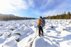 Hiker with backpack on the snow field of stones at the way to the rocky mountains Stock Image