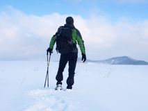 Hiker with backpack snowshoeing  in deep drift. Man with walk in hill. Royalty Free Stock Photo