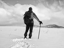 Hiker with backpack snowshoeing  in deep drift. Man with walk in hill. Stock Photo