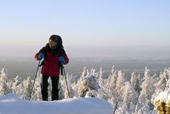 Traveler rises to the top of the mountain in winter. Hiker with a backpack in sports clothes rises to the top of the mountain against the background of a winter Royalty Free Stock Photos