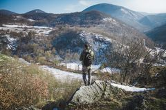 Hiker with backpack standing on top of cliff in winter mountains royalty free stock image