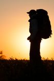 Hiker with backpack standing in the field Stock Photography