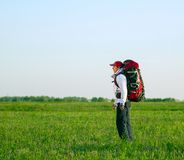 Hiker with backpack standing in the field Royalty Free Stock Images