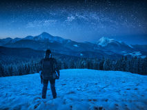 Hiker with backpack standing on a hill covered with snow. And enjoy starry sky above the winter mountain valley Royalty Free Stock Image