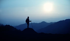 Hiker with backpack standing on the hill Royalty Free Stock Image