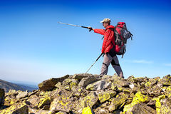 Hiker with backpack standing in the mountains and enjoying the v Royalty Free Stock Image