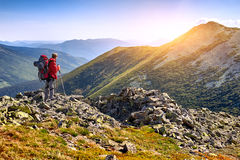 Hiker with backpack standing in the mountains and enjoying the v Royalty Free Stock Images