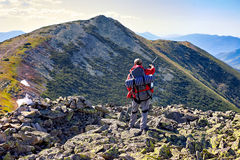 Hiker with backpack standing in the mountains and enjoying the v Stock Images