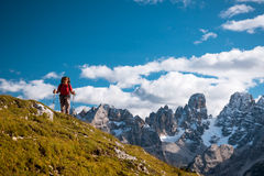 Hiker with backpack standing on path in mountains Royalty Free Stock Images