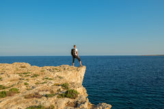 Hiker with backpack standing on the rocky coast Cape Greco Royalty Free Stock Image