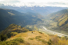 Hiker with backpack standing on top of a mountain and enjoying Colorful autumn landscape in the mountain village.  Royalty Free Stock Photo