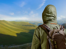 Hiker with backpack standing on top of a mountain and enjoying n Stock Photography