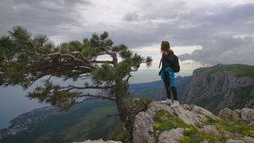 Hiker with backpack standing on top of the mountain and enjoying valley view. Girl in a leather jacket and black jeans, standing on the edge of the cliff in stock footage