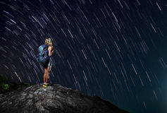 Hiker. With backpack standing on top of a mountain with star trails on the backgound (real stars Royalty Free Stock Image