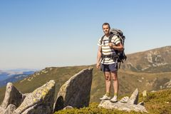 Hiker with backpack standing on top of the mountain. Tourist man near big stone rocks on Carpathian mountains ridge in Ukraine. Travel, trekking and active way Stock Image