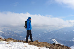 Hiker with backpack is standing in the winter mountains and look Stock Photo