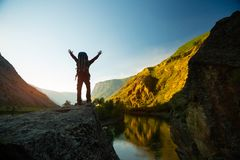 Hiker with backpack stands on a cliff royalty free stock images
