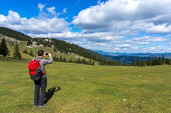 Hiker with backpack taking pictures Royalty Free Stock Photos