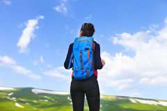 Hiker with backpack on top of mountain and enjoying valley view Royalty Free Stock Images