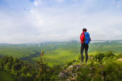 Hiker with backpack on top of mountain and enjoying valley view stock photos