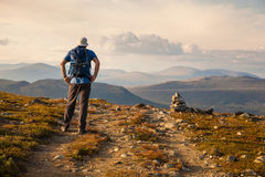 Hiker with backpack traveling in Norway mountains Dovre Royalty Free Stock Images