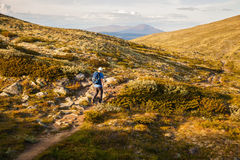 Hiker with backpack traveling in Norway mountains Dovre Stock Photo