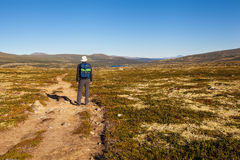 Hiker with backpack traveling in Norway mountains Dovrefjell Royalty Free Stock Images