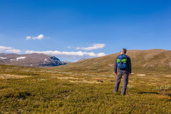 Hiker with backpack traveling in Norway mountains Dovrefjell Royalty Free Stock Photo