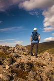 Hiker with backpack travelling in Norway mountains Dovre.  Royalty Free Stock Images