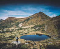Hiker with backpack and trekking poles on a lake. Instagram styl Royalty Free Stock Image
