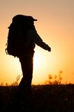 Hiker with backpack walking in the field Stock Images