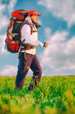 Hiker with backpack walking in the field Royalty Free Stock Images