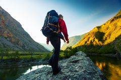 Woman hiker stands with backpack. Hiker with backpack walks towards the top of the stone located in the valley with mountains covered by a morning sunrise light stock photography