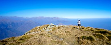 Hiker with backpack watching mountain panorama Stock Images