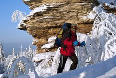 Tourist with a backpack in a windproof mask in the winter mountains. Hiker with a backpack in a windproof mask rises uphill in winter against a backdrop of a stock images