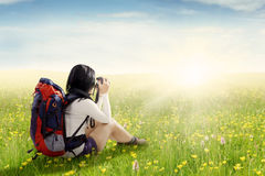 Hiker with bag taking pictures on meadow Royalty Free Stock Photography