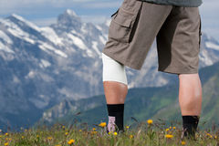 Hiker with bandage. Elderly hiker with bandage on knee in Swiss Alps Royalty Free Stock Images