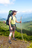 Hiker with bandage on knee. Young hiker with bandage on knee and cane in hand in mountains. Male wearing shorts on top of mountain with wrapped injured knee with Stock Photography