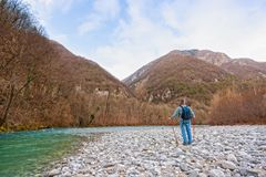 Hiker on the bank of a river. Walking toward mountain. Hiker on the bank of a river. Trekking toward  mountain. Rambler about 60 years old Stock Photo