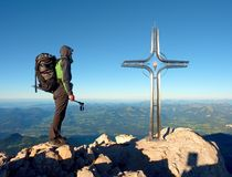 Hiker at big crucifix on mountain peak. Iron cross at Alps mountain top. Stock Image