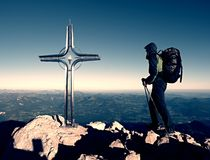 Hiker at big crucifix on mountain peak. Iron cross at Alps mountain top. Stock Photo