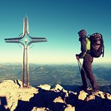 Hiker at big crucifix on mountain peak. Iron cross at Alps mountain top. Royalty Free Stock Photography