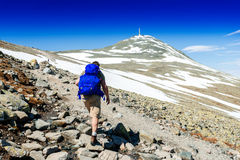 Hiker with big traveling rucksack looking forward on the mountai Royalty Free Stock Images