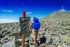 Hiker with big traveling rucksack looking forward on the mountai Stock Photo