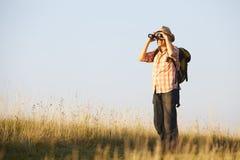 Hiker with binoculars on meadow Stock Image